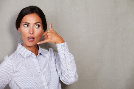 attractiveness: Suprised adult female gesturing a call with open mouth and formal clothing on grey texture background - copy space Stock Photo