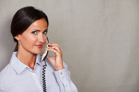 attractiveness: Customer service woman in formal clothing speaking on phone and looking at camera on grey texture background