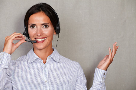 formal shirt: Brunette lady secretary speaking through headset and smiling in formal shirt while looking at camera on grey texture background