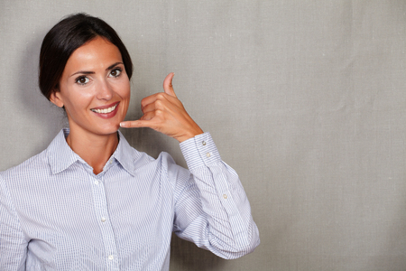 formal clothing: Well-dressed adult female with phone call gesture while smiling and looking at camera in formal clothing on grey texture background