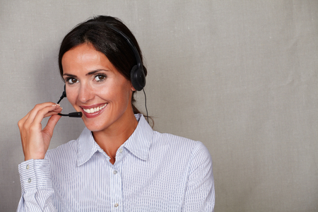 back straight: Smiling straight hair lady operator using headset in formalwear and hair back while looking at camera on grey texture background