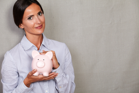 button down shirt: Financial woman holding pink piggy bank in button down shirt and looking at camera on grey texture background Stock Photo