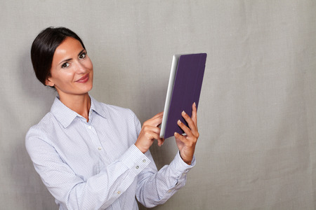 attractiveness: Smiling pretty young lady holding tablet while looking at camera in formal clothing against grey texture background
