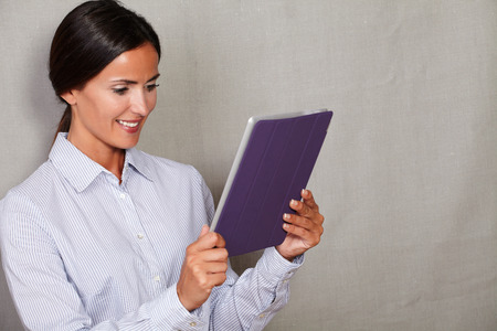 formalwear: Smiling businesswoman holding and reading tablet in formalwear on grey texture background