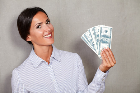 toothy smile: Brunette female holding and showing dollars with happy face and toothy smile while looking at camera on grey texture background
