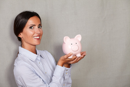 formal clothing: Straight hair woman holding pink piggy bank with toothy smile and formal clothing while looking at camera on grey texture background Stock Photo