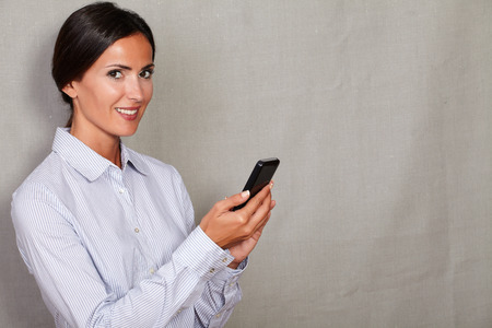 caucasian ethnicity: Caucasian ethnicity lady holding mobile phone in formal clothing and looking at camera against grey texture background