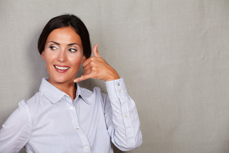 button down shirt: Young businesswoman with toothy smile while gesturing a call and looking away in button down shirt on grey texture background - copy space