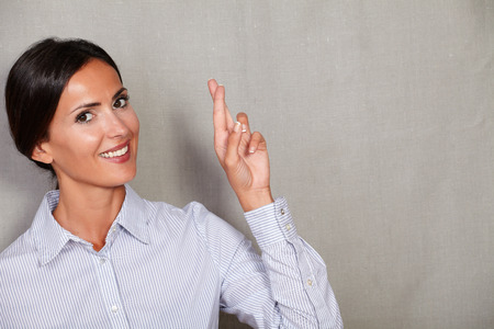 formalwear: Smiling businesswoman in formalwear crossing fingers and smiling while looking at camera on grey texture background
