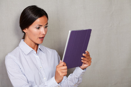 attractiveness: Brunette female looking shocked while holding and reading on tablet in business shirt on grey texture background Stock Photo