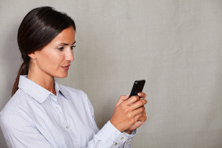 Straight hair lady using cellular phone and texting in button down shirt and hair back on grey texture background
