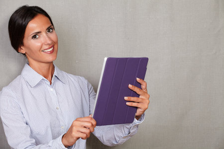 formal clothing: Caucasian ethnicity lady in formal clothing holding tablet and smiling while looking at camera on grey texture background Stock Photo