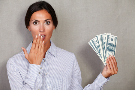 Surprised adult woman with hand to her mouth while showing money and looking at camera against grey texture background