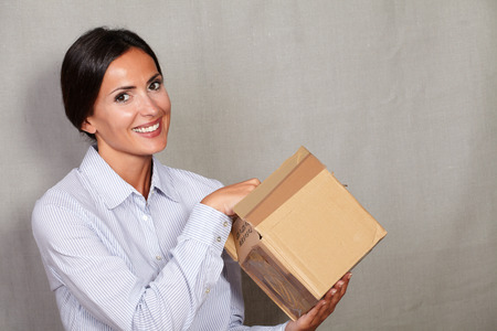 caucasian ethnicity: Caucasian ethnicity female opening parcel and smiling while looking at camera in button down shirt on grey texture background Stock Photo