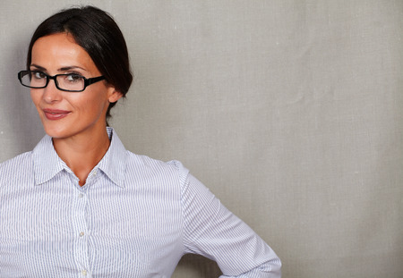 formal clothing: Young businesswoman wearing glasses and smiling in glasses and formal clothing while looking at camera on grey texture background