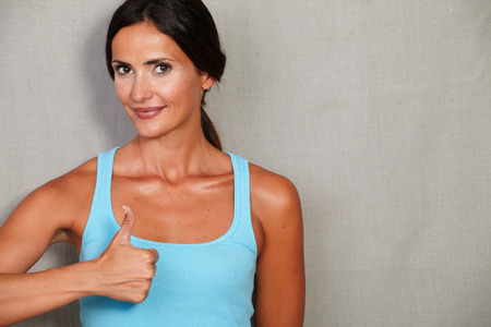 sport wear: Fitness lady showing thumb up ok sign in sport wear while smiling and looking at camera on grey texture background