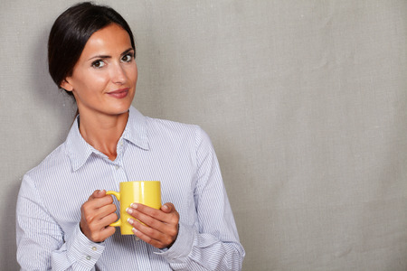 formal clothing: Straight hair brunette woman holding yellow mug and looking at camera in formal clothing on grey texture background