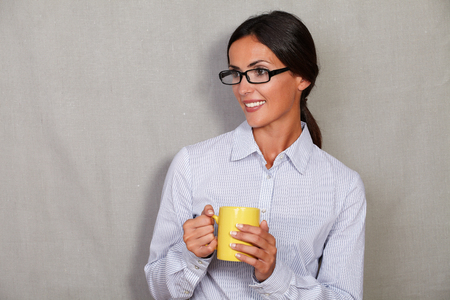 formal clothing: Smiling lady wearing glasses and formal clothing while holding mug with hot drink and looking away on grey texture background - copy space
