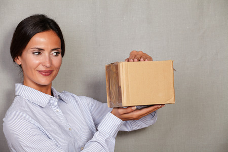 attractiveness: Brunette lady smiling while opening package in formal clothing and hair back on grey texture background