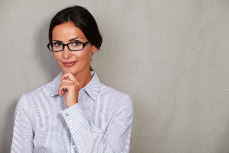 hair back: Straight hair lady with hand on chin and hair back while looking at camera and smiling in formal shirt and glasses on grey texture background