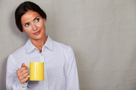button down shirt: Well-dressed lady standing in button down shirt and holding yellow mug while looking away on grey texture background - copy space Stock Photo
