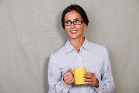 button down shirt: Caucasian ethnicity female in glasses and button down shirt holding mug and looking away against grey texture background - copy space