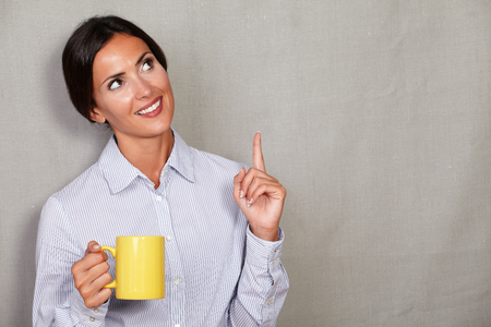 toothy smile: Straight hair lady pointing up and looking away with toothy smile while holding yellow mug on grey texture background - copy space Stock Photo