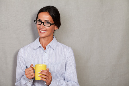 formal shirt: Toothy smile lady with glasses holding mug and looking at camera in formal shirt on grey texture background Stock Photo