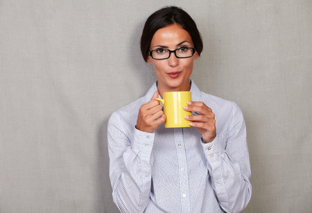 formal clothing: Straight hair brunette lady blowing hot drink while holding mug in formal clothing and glasses and looking at camera on grey texture background Stock Photo