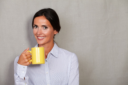 button down shirt: Smiling adult female in button down shirt holding hot drink with toothy smile while looking at camera on grey texture background Stock Photo