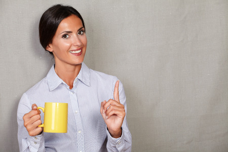 formal shirt: Young businesswoman smiling with witticism and holding hot drink while looking at camera in formal shirt on grey texture background
