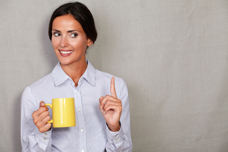 formal wear: Straight hair lady smiling with toothy smile pointing up while holding mug in formal wear and looking away on grey texture background - copy space