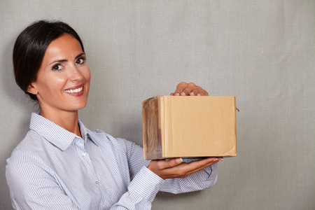 formal clothing: Young lady with toothy smile holding parcel while looking at camera in formal clothing on grey texture background