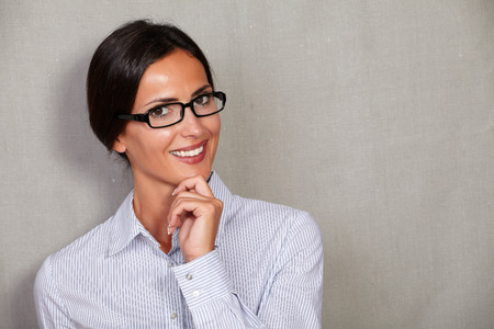formal clothing: Happy adult woman in glasses and formal clothing smiling with hand on chin and looking at camera on grey texture background