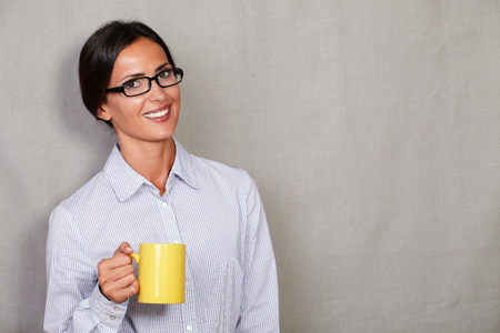 button down shirt: Long hair woman with glasses holding coffee and smiling while looking at camera in button down shirt against grey texture background