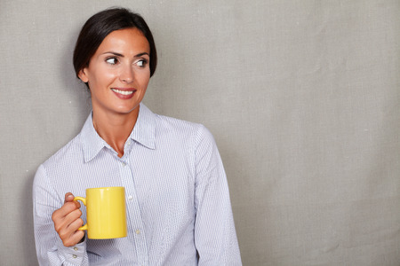 formal wear: Satisfied adult female holding yellow mug while smiling with toothy smile and looking away in formal wear on grey texture background - copy space