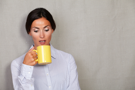 formal clothing: Brunette lady holding and looking at empty mug in formal clothing against grey texture background Stock Photo