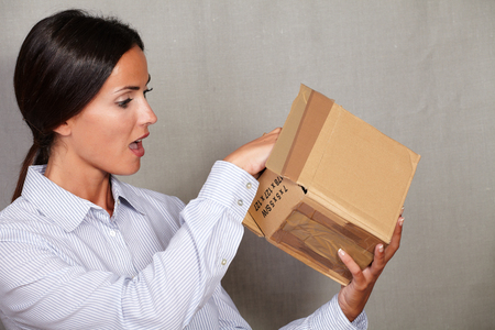 button down shirt: Straight hair female in button down shirt looking surprised while open a box with open mouth on grey texture background