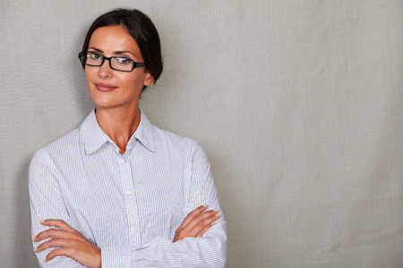 formal shirt: Straight hair lady smiling with arms crossed and looking at camera in glasses and formal shirt on grey texture background Stock Photo