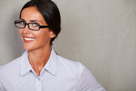 formal shirt: Young woman in close up head and shoulders portrait wearing glasses and formal shirt while looking at camera with toothy smile against grey texture background