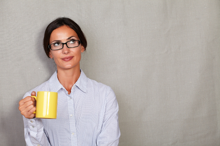button down shirt: Pensive adult lady holding coffee mug in button down shirt and glasses while looking away thoughtful on grey texture background - copy space