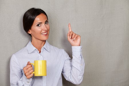 button down shirt: Smiling female with hot drink pointing up and wearing button down shirt while looking at camera on grey texture background