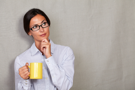 formal wear: Wondering businesswoman with hand on chin holding coffee mug while thinking and looking away in glasses and formal wear on grey texture background - copy space