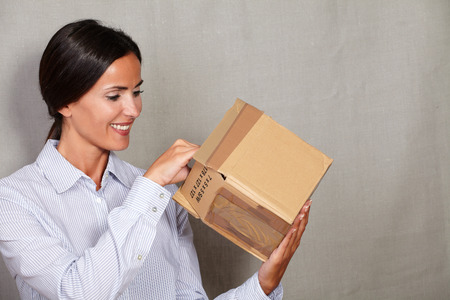 formal clothing: Toothy smile woman standing and opening parcel in formal clothing on grey texture background