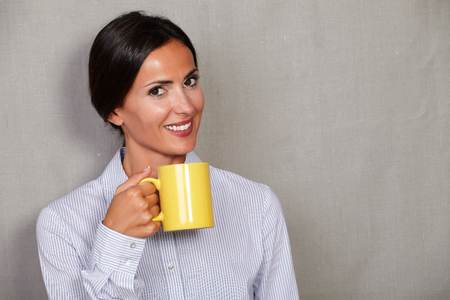 button down shirt: Happy young lady holding yellow mug with hot drink and smiling while looking at camera in button down shirt on grey texture background