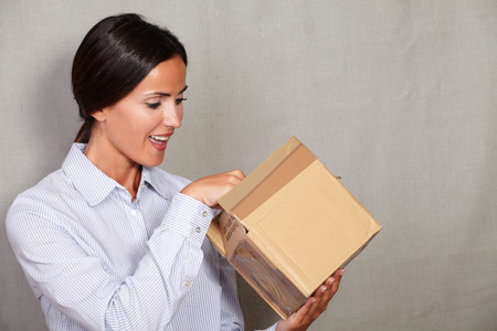 formal wear: Well-dressed female with open mouth while open a box in formal wear and hair back against grey texture backgroung Stock Photo