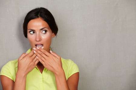 caucasian ethnicity: Caucasian ethnicity woman with hands to mouth while looking away shocked and surprised in green blouse against grey texture background - copy space Stock Photo