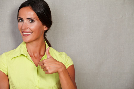 back straight: Straight hair female showing thumb up and toothy smile while looking at camera in casual clothing and hair back on grey texture background Stock Photo