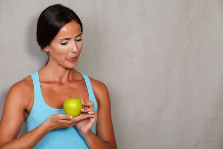 sport wear: Healthy female licking his lips while looking and holding apple in sport wear on grey texture background Stock Photo