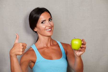sport wear: Standing young woman showing thumb up while holding apple in sport wear and looking at camera against grey texture background